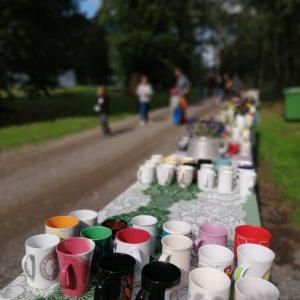 Katajistonranta Mielensäpahoittaja festivaalit kahvimukit pöydällä