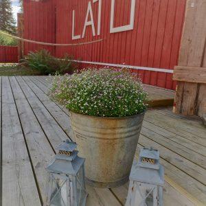 Tapahtumalato julkisivu latohäät kukkakoristeet ja lyhty terassilla
